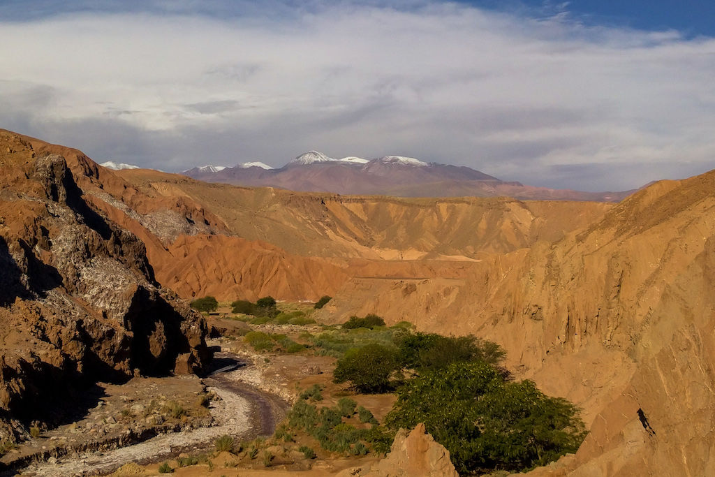 Desert road, jagged red hills, and the Andes Mountains against a cloudy sky