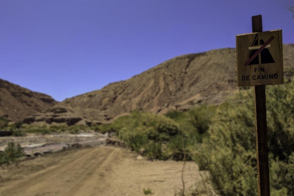 "A sign reading ""Fin de Camino"" on an empty desert road"