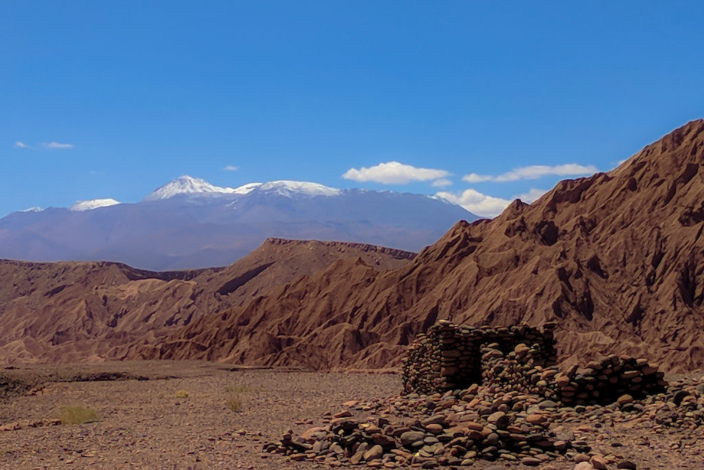 Incan ruins and rubble with red desert hills and the Andes Mountains in the distance