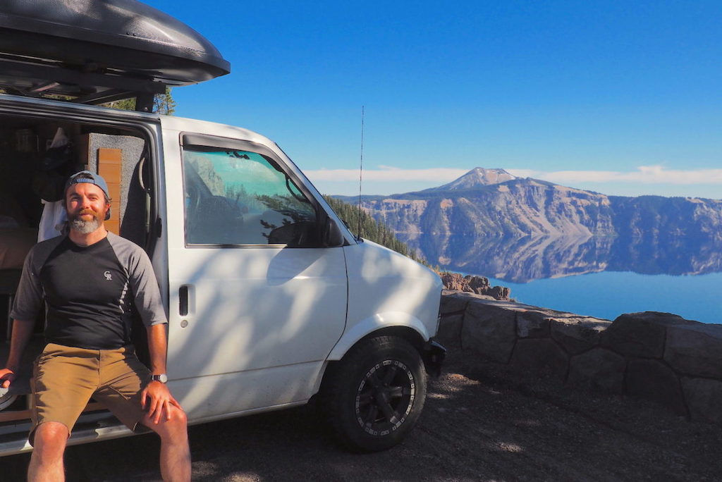 Man sitting in his camper van with a backdrop of Crater Lake, Oregon
