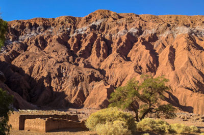 Red, jagged desert hills with white salt deposits and Incan ruins at the base