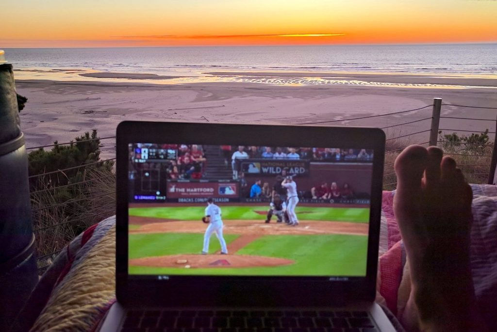 Laptop watching a Rockies baseball game with a backdrop of a Sunset over the Oregon coast