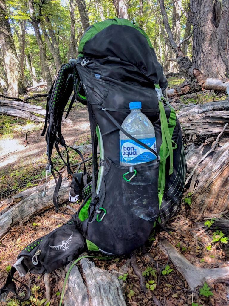 A green and black hiking backpack with a blue water battle in the side propped up in the forest