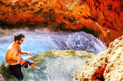 A man sitting in a natural pool of water above Mooney Falls in Havasupai, Arizona