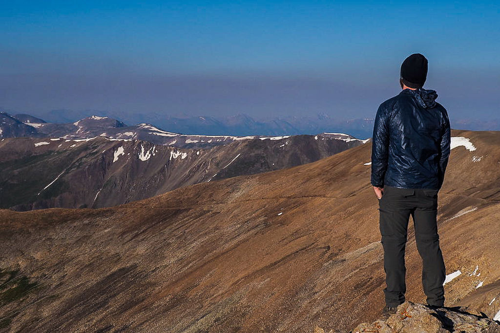 A man stands atop Mount Lincoln in Colorado look off to the horizon