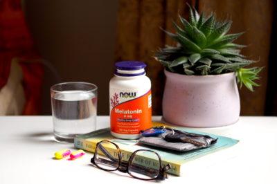 Water, earplugs, glasses, melatonin, keys, wallet, and a plant on a bedside table in a hostel