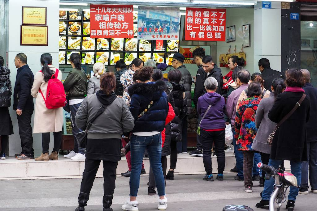 Line of about 30 people waiting to get treats from a bakery in Chengdu, China