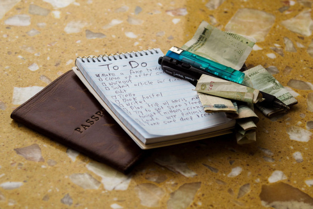 To-do list, pen, passport, money, and a lighter all in a pile