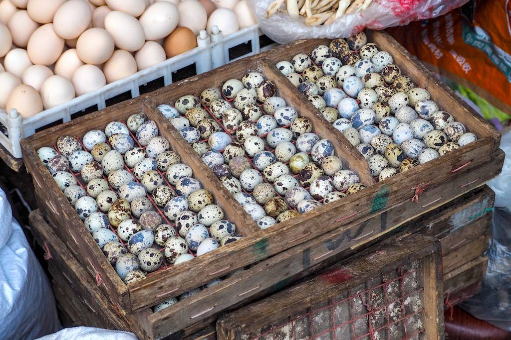 Wooden box full of colorful quail eggs in an outdoor market