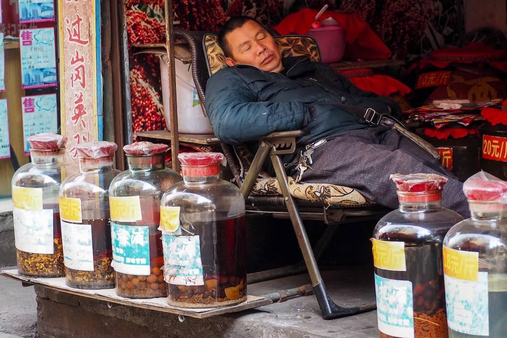 Man sleeping in chair by jars of baijiu in an outdoor food market