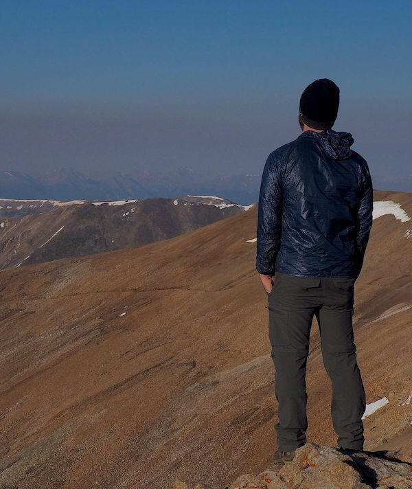 Man looking off to the horizon as he stands atop a mountain