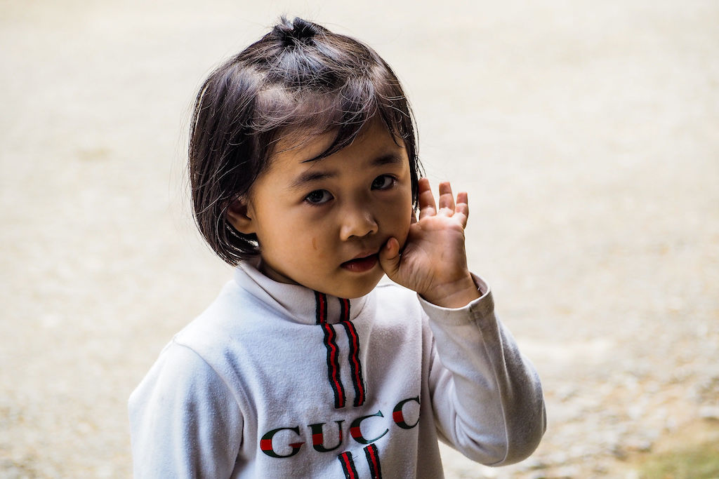 A little girl with short black hair and brown eyes with her hand on her face