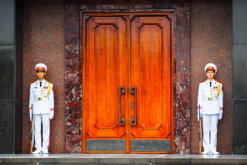 Two soldiers, dressed in white with guns at their side stand stoically next to wooden doors