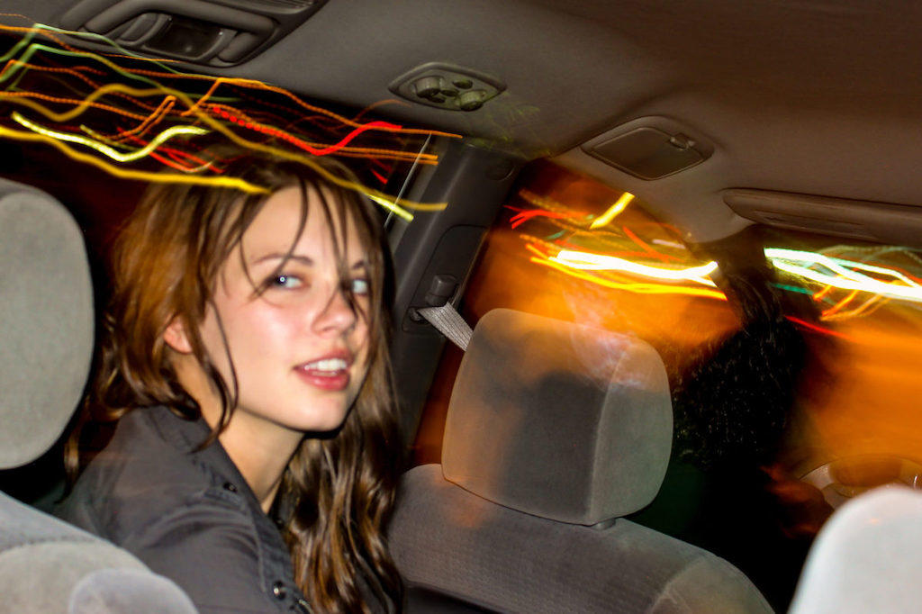 Woman in a car at night looking over her shoulder at the camera