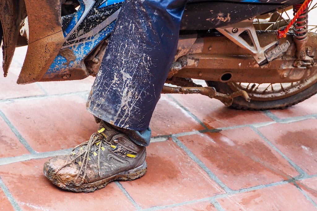 A boot, leg, and motorbike caked with mud