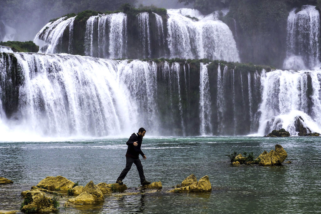 A man walks across rocks with large waterfalls flowing in the background