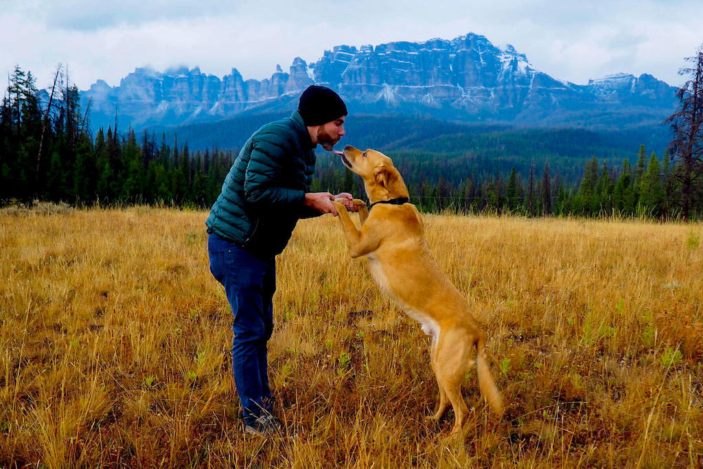 Man and a dog standing up together in front of the Teton mountain range in Wyoming, U.S.A.
