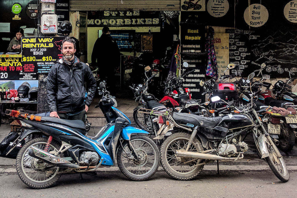 A man standing behind a blue motorbike in front of a shop called Style Motorbikes