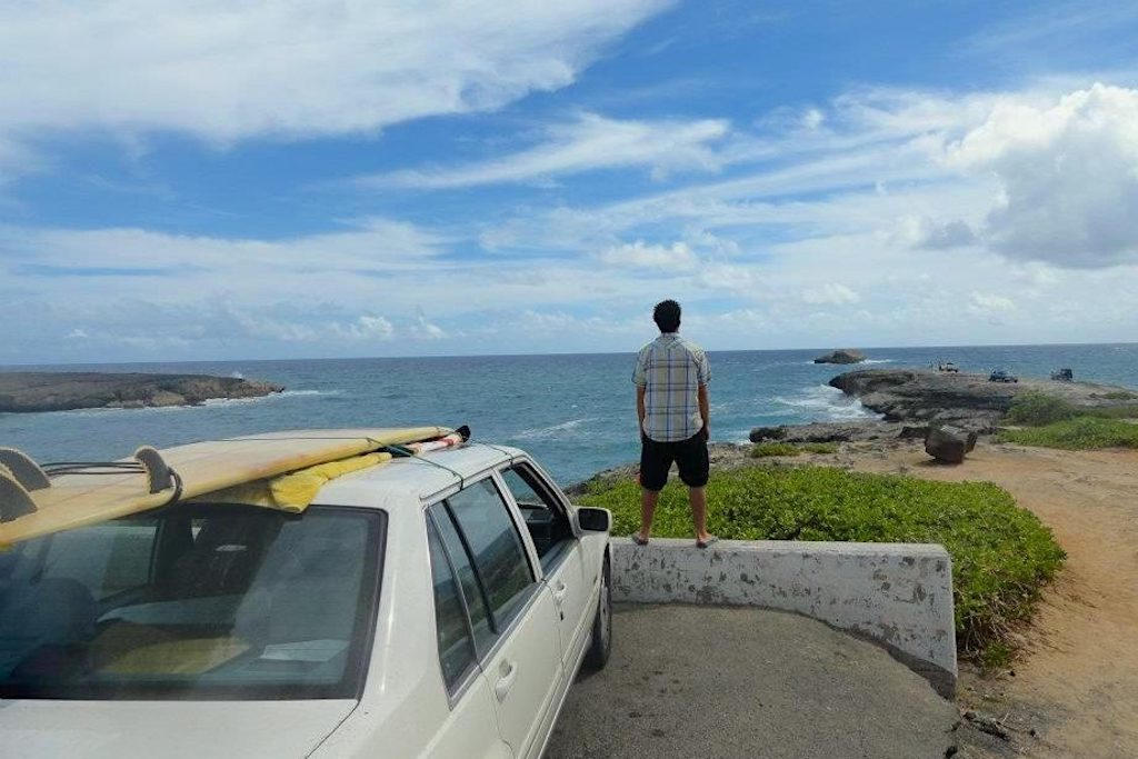 Man standing next to his car with a surfboard on the roof staring out to the Pacific Ocean