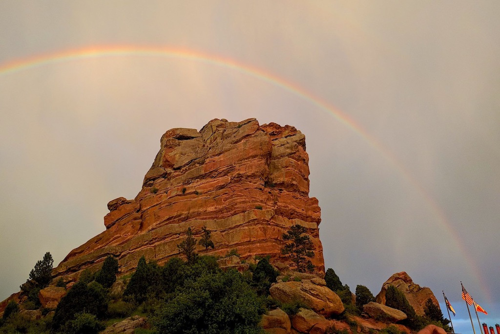 Rainbow over a red rock outcropping against a cloudy sky