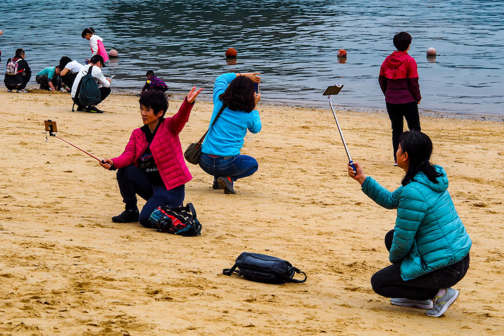 Tourists crouched on a beach taking photos with selfie sticks