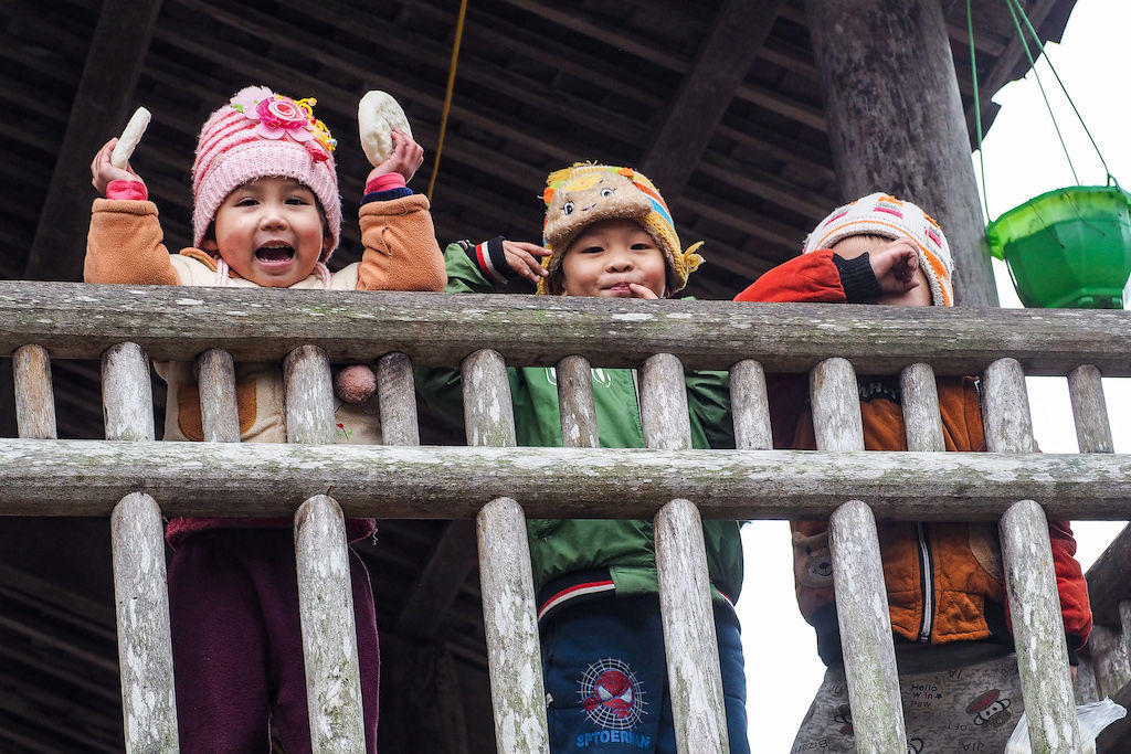 Three children smile and wave while looking over a wooden railing