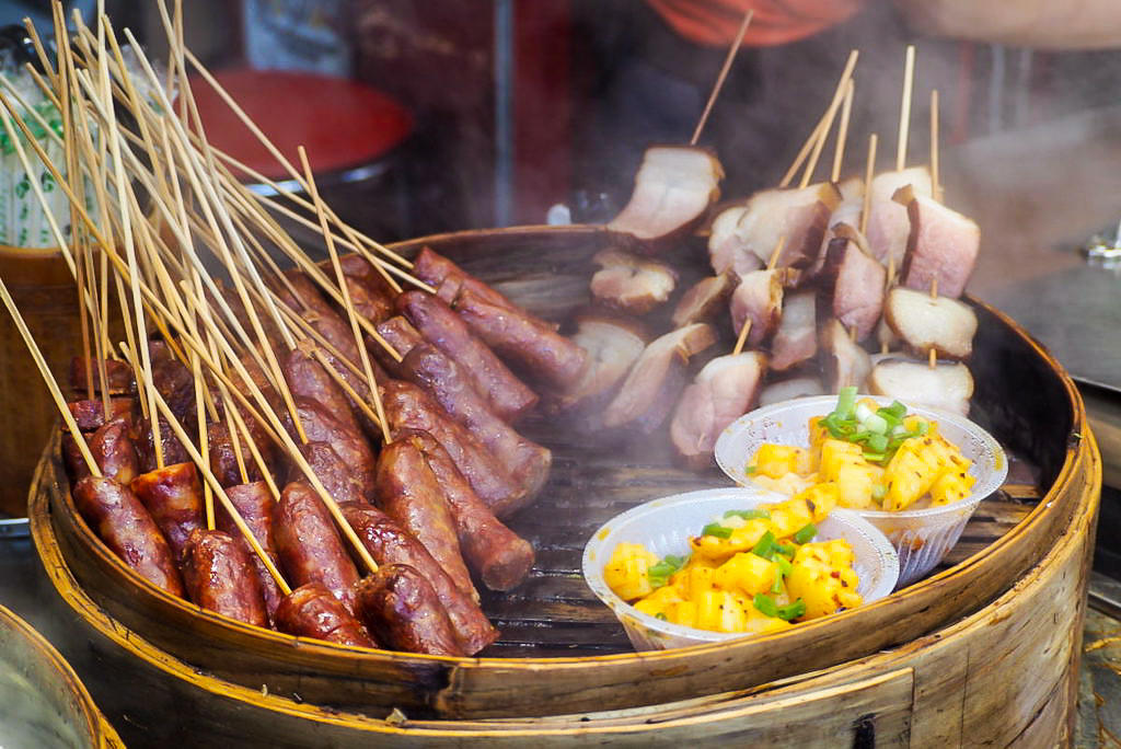 A steaming wooden basket full of skewered meat and potatoes