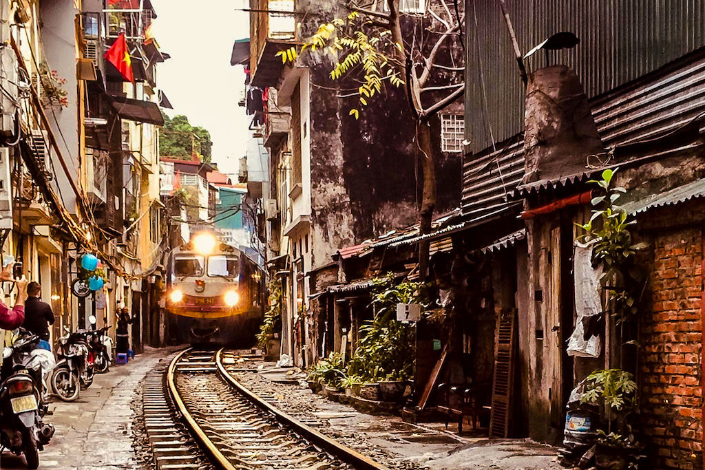 A train squeezes through a narrow alley as it moves nearer down the tracks